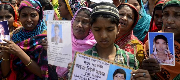 Relatives of the Rana Plaza victims demonstrate with photos of their deceased loved ones.