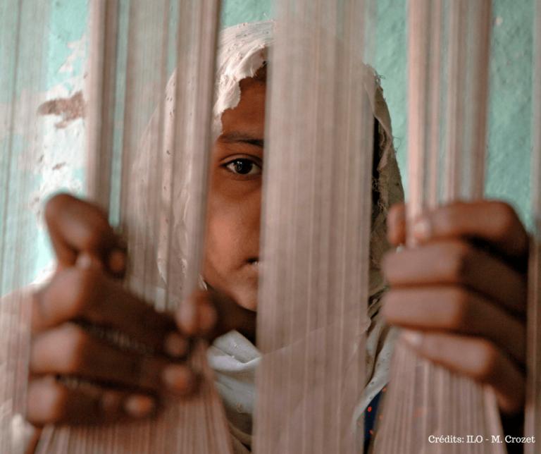 Jeune fille voilée derrière des barreaux